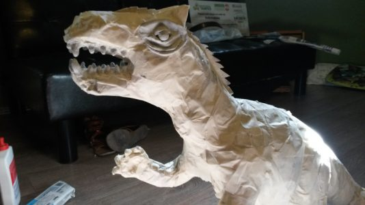 Adding teeth made from air dry clay to the paper mache dinosaur.