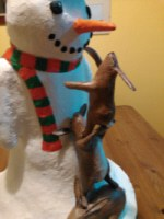 Paper mache snowman with rabbits trying to steal his nose.