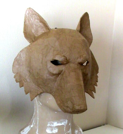 Paper mache wolf mask covered with brown paper.