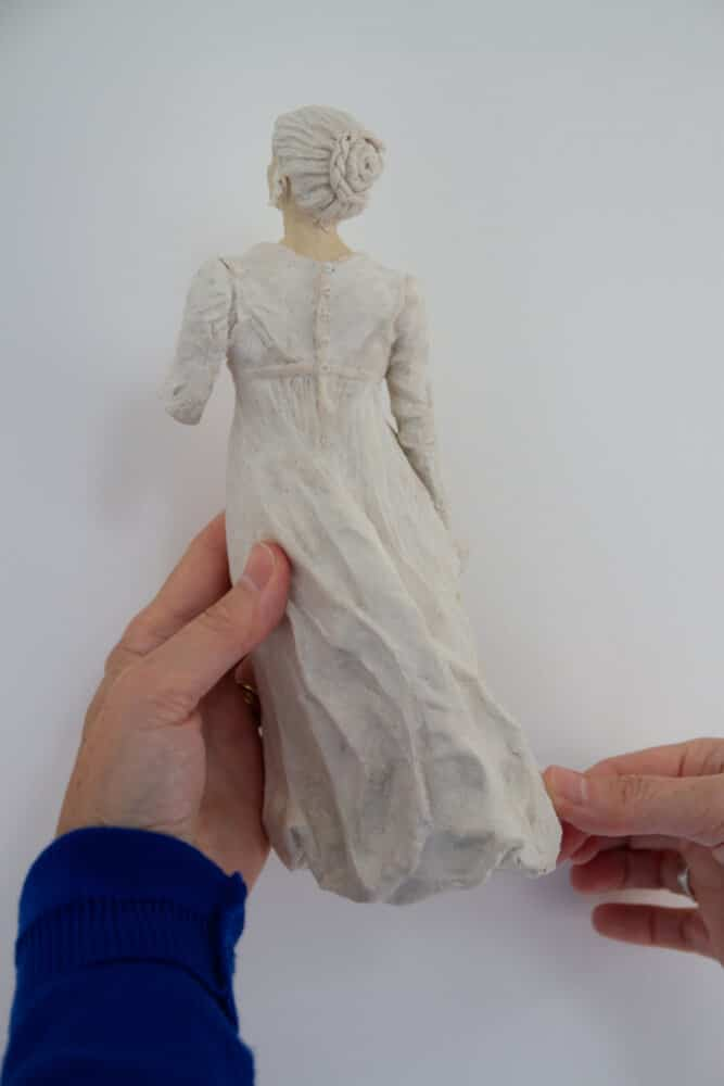 Adding buttons to paper mache clay figure sculpture