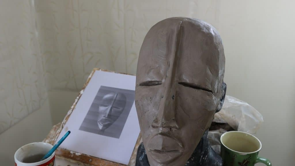 Make a paper mache African mask, starting with a clay form.