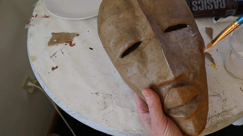 Sealing the paper mace African mask with clear gesso.