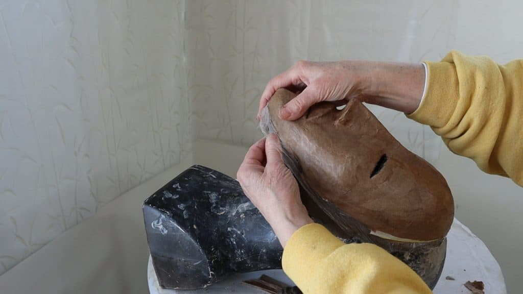 Pull the paper mache off the mask form.