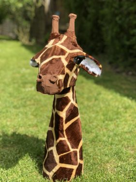 Paper mache giraffe head covered with faux fur.