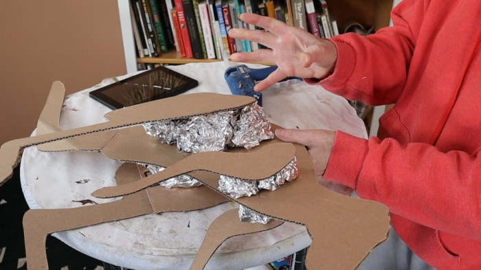 Reinforcing the paper mache animal sculpture's armature with more foil and hot glue.