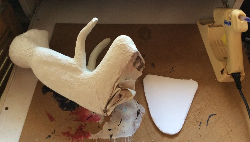 Stuffing the paper mache clay figures for internal support.