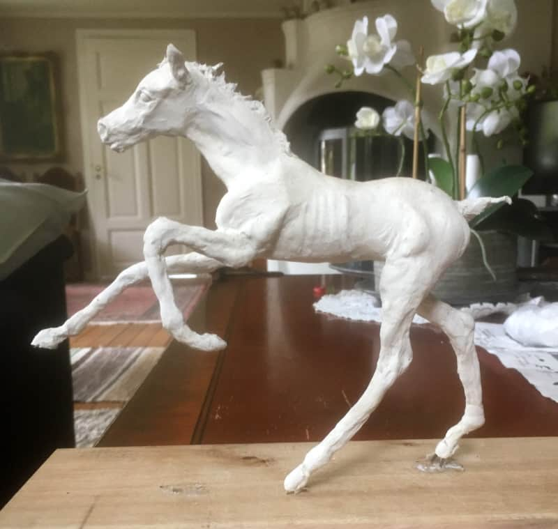 Attaching the paper mache foal to a base.