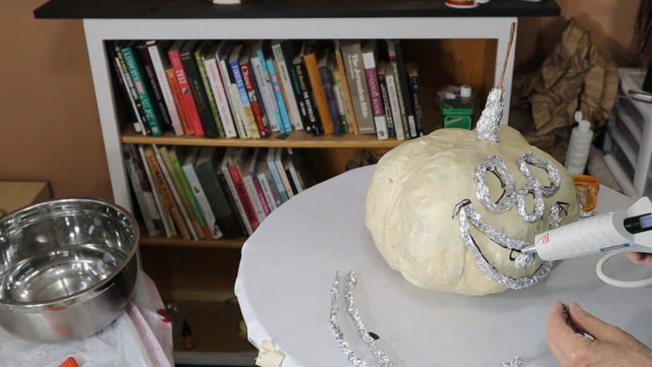 Use foil to outline the features on your Halloween pumpkin.
