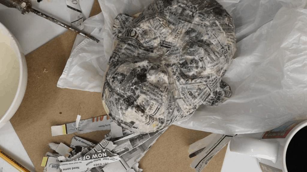 Add one layer of paper mache to your orangutan