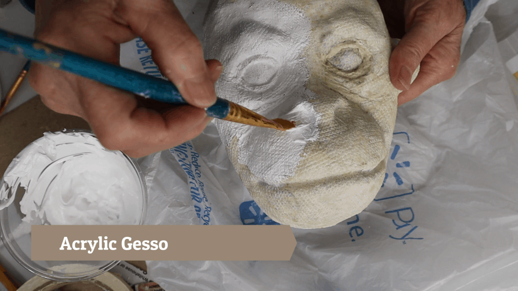 Brushing acrylic gesso over the baby orangutan