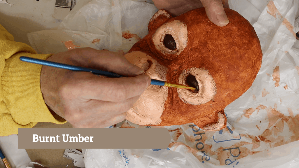 Painting the baby orangutan's eyes