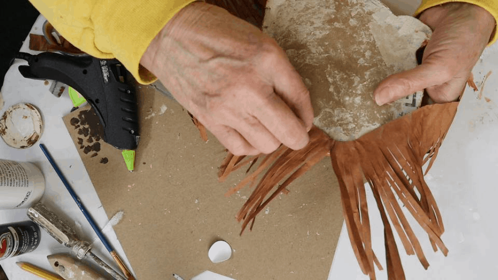 Adding hair to the paper mache orangutan