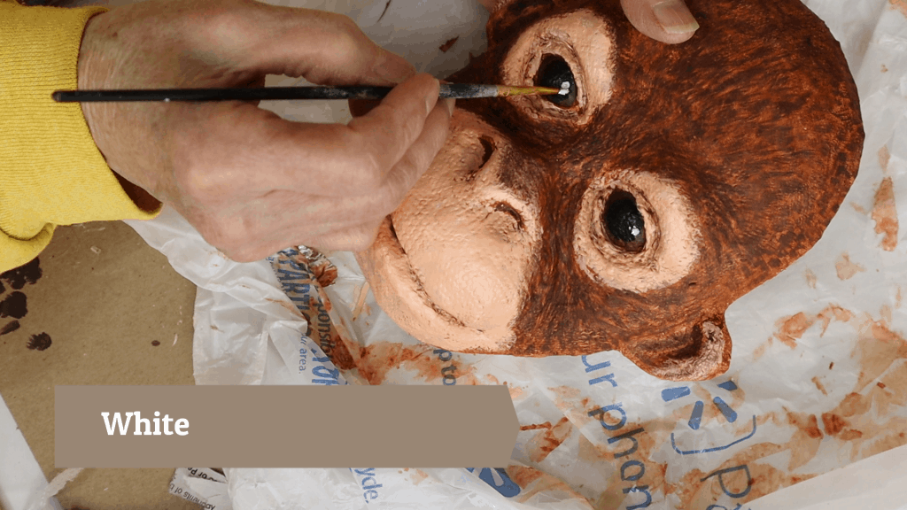 White reflection in the baby orangutan's eyes.