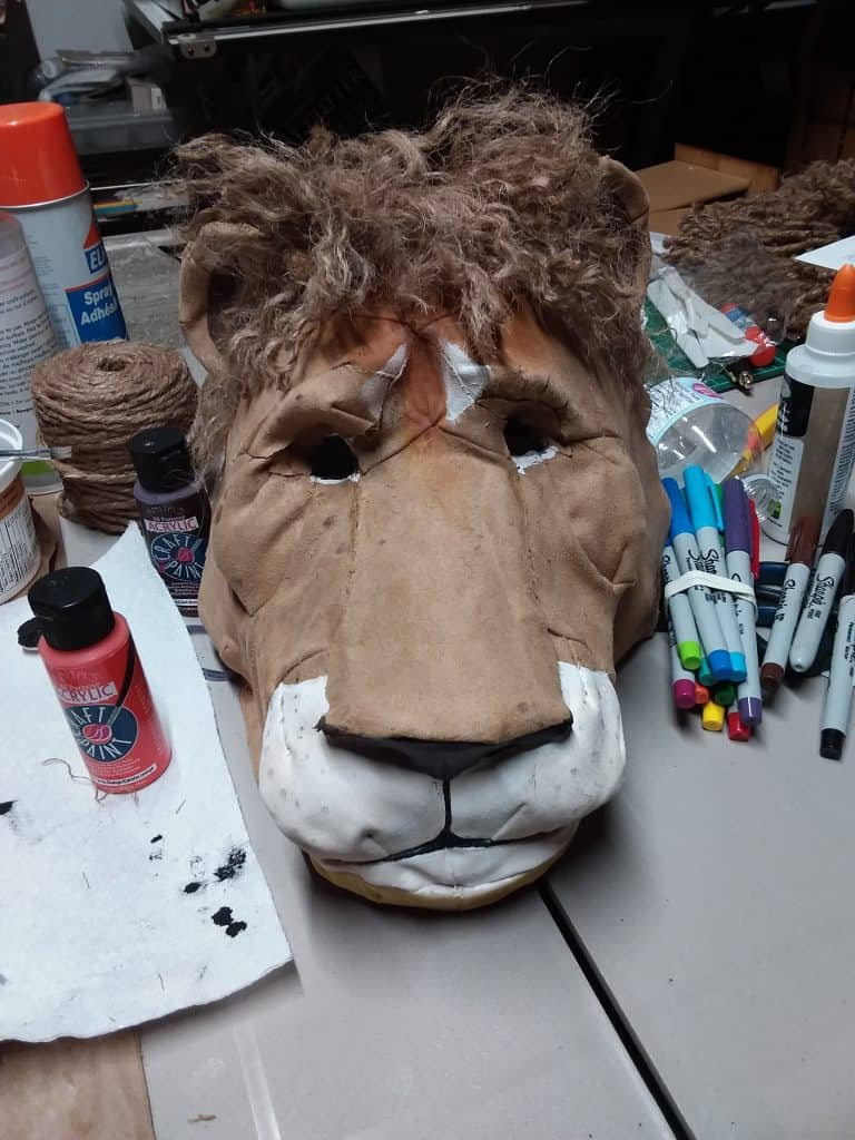Adding a mane to the fabric lion head.