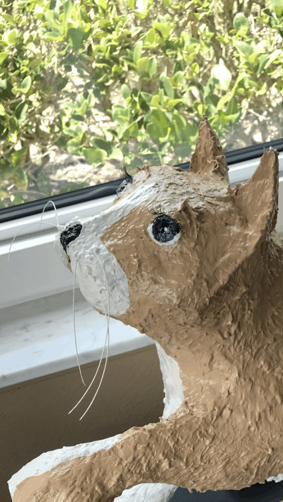 Whiskers and eyelashes on paper mache cat