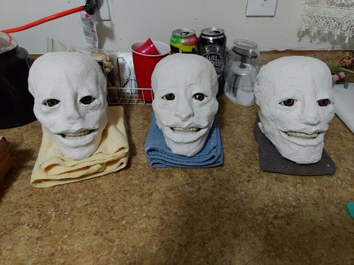Paper mache faces sculpted over skulls