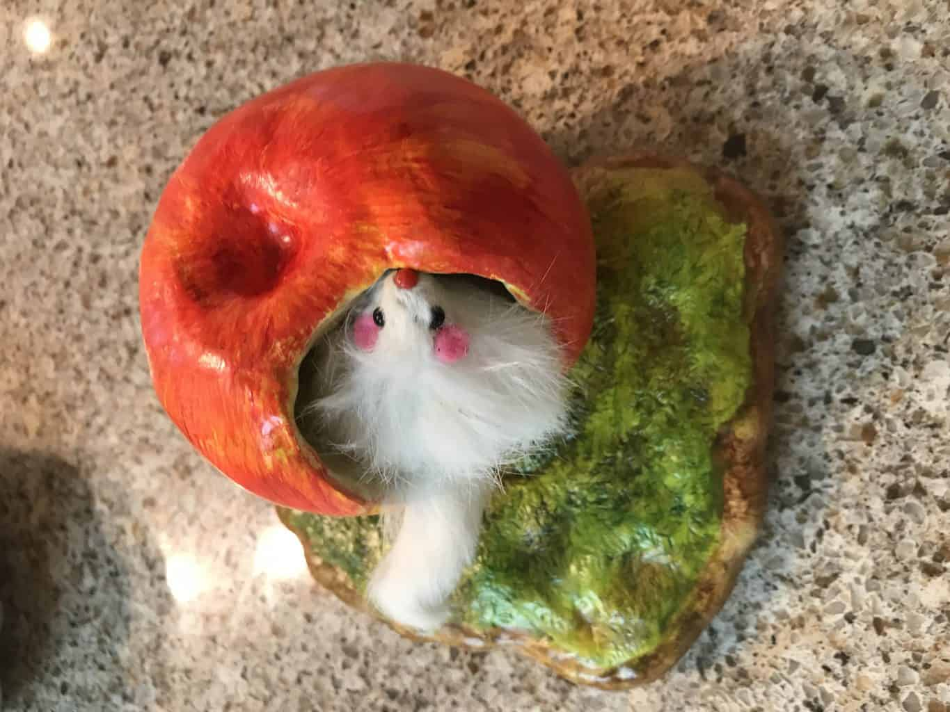 Mouse playing inside an apple