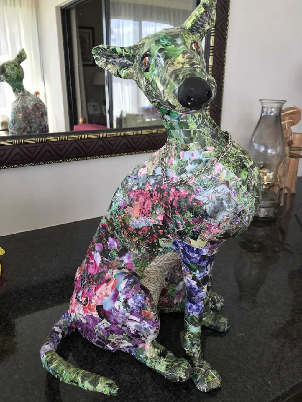 Paper mache dog covered in small pieces of floral paper from old magazines.