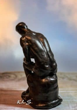 man on a rock a la Penceur of Rodin
