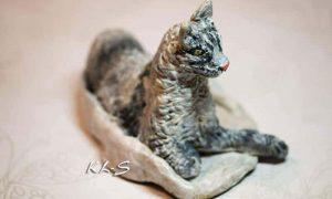 Paper mache cat on a blanket