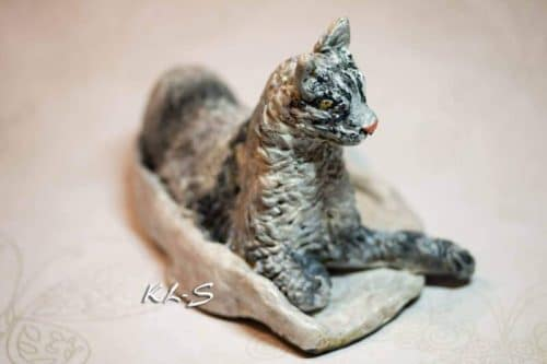 Paper mache cat on a blanket
