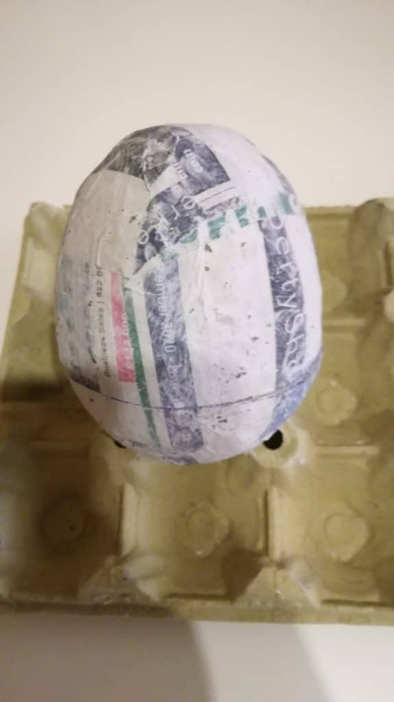 Cover the egg with paper mache