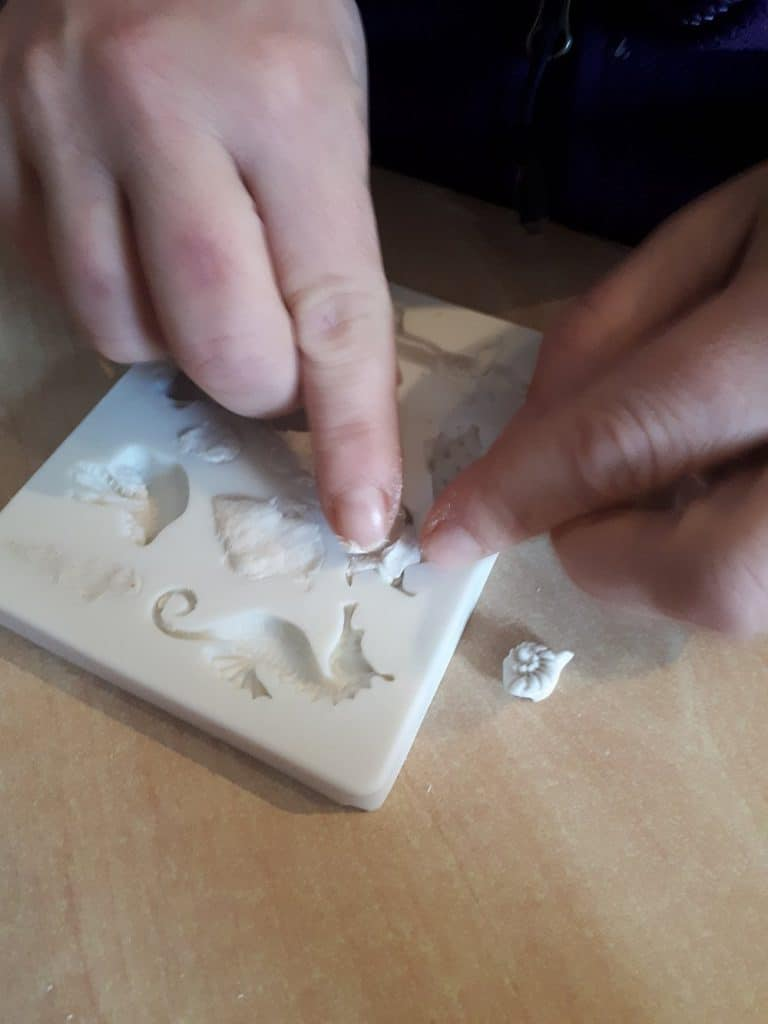 filling the moulds with the dry powder clay